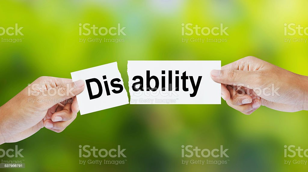 Businessman tearing the word Disability for Ability stock photo