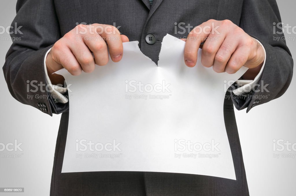 Businessman tearing white blank paper stock photo