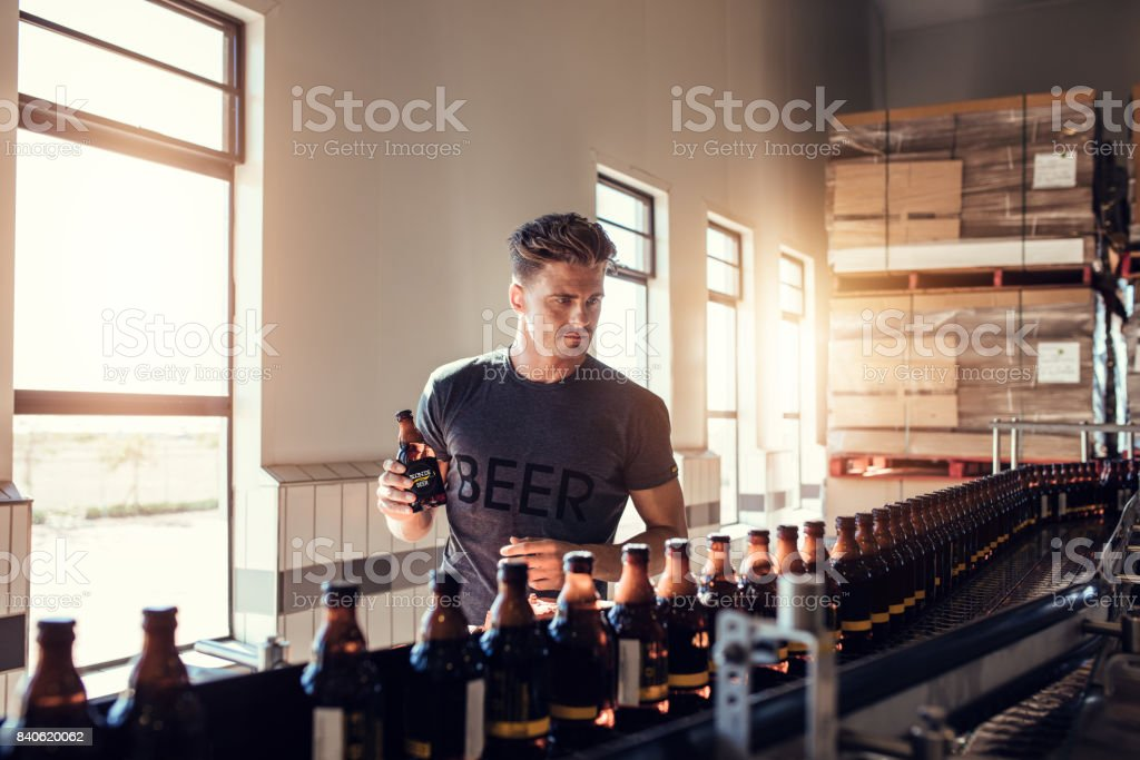 Businessman testing the beer bottle at brewery stock photo