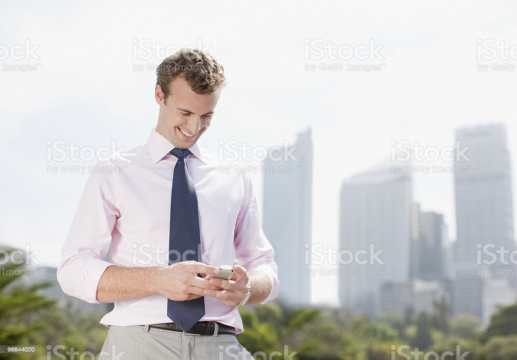 Businessman text messaging on cell phone outdoors royalty free stockfoto
