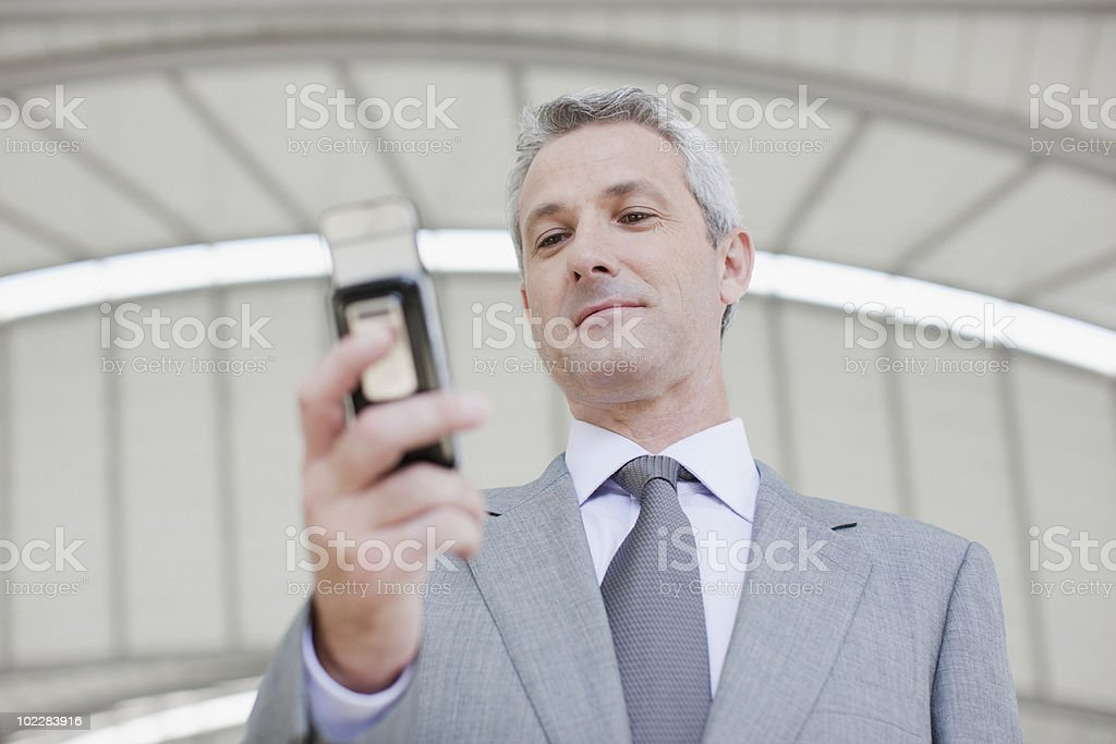 Businessman text messaging on cell phone royalty-free stock photo