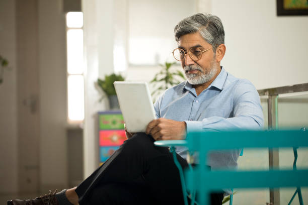 Businessman text messaging using digital tablet stock photo