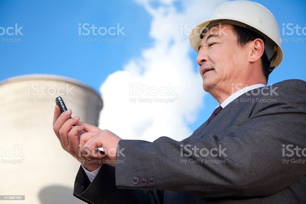 Businessman texting at power plant stock photo