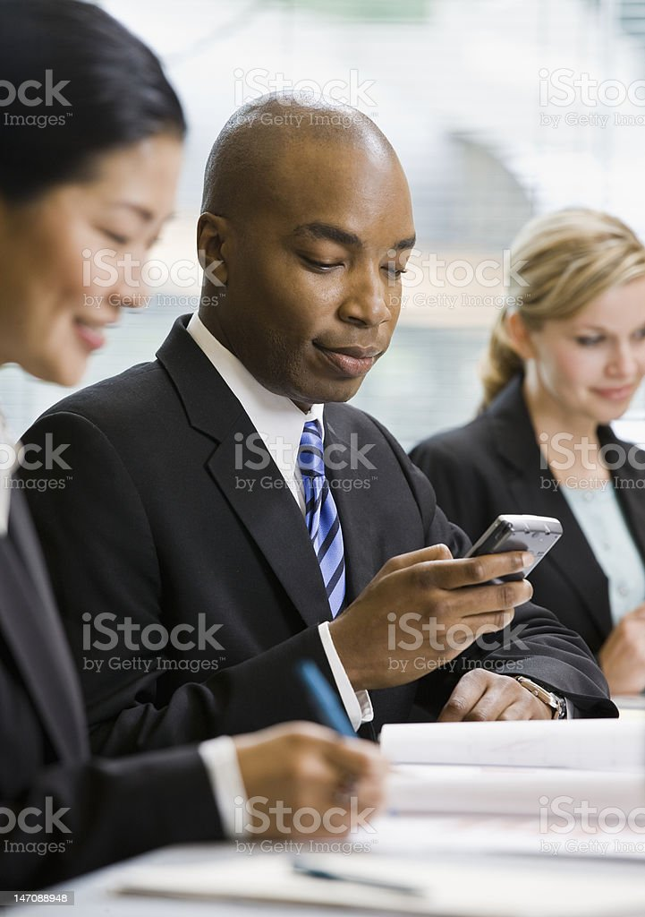 Businessman Texting in a Meeting - Royalty-free 20-29 Years Stock Photo