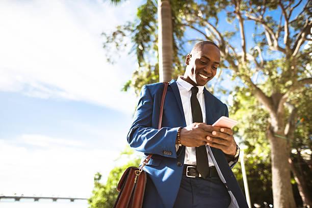 businessman texting in miami - outdoor handy stock-fotos und bilder