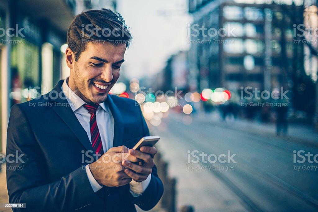 SMS uomo d'affari all'aperto di sera - Foto stock royalty-free di Abbigliamento casual