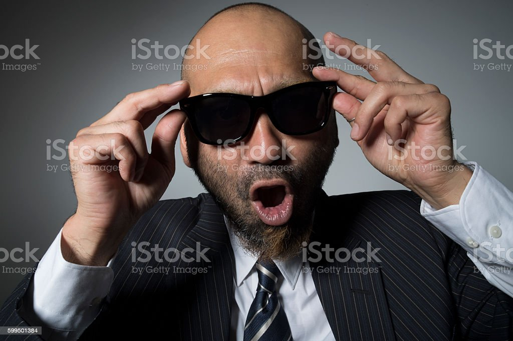 Businessman that opened the mouth is wearing sunglasses. stock photo