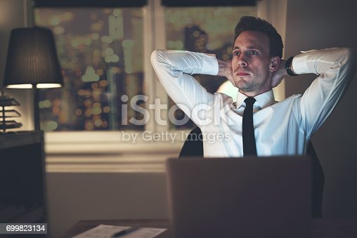 istock Businessman thinking at office working overtime 699823134