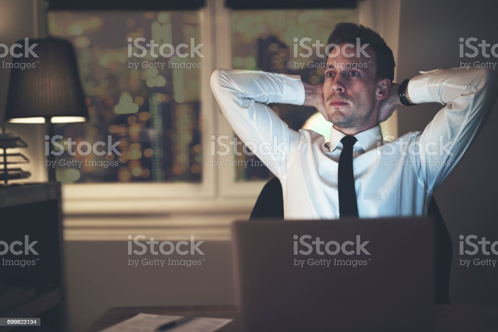 Businessman thinking at office working overtime stock photo