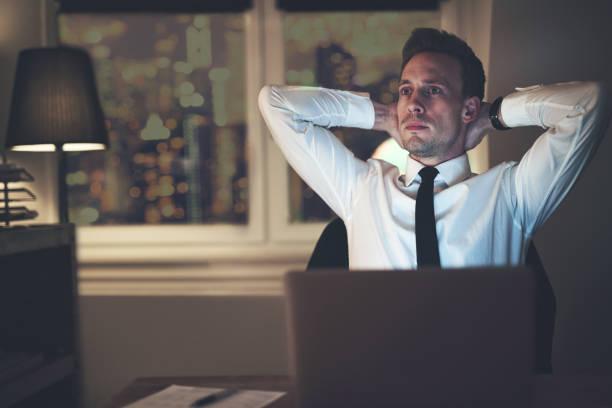 残業オフィスで考えているビジネスマン - パラリーガル ストックフォトと画像