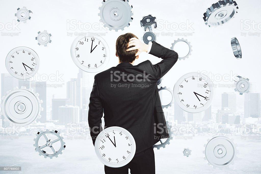 Geschäftsmann denkt über die Zeit umgeben von Uhr und Getriebe – Foto