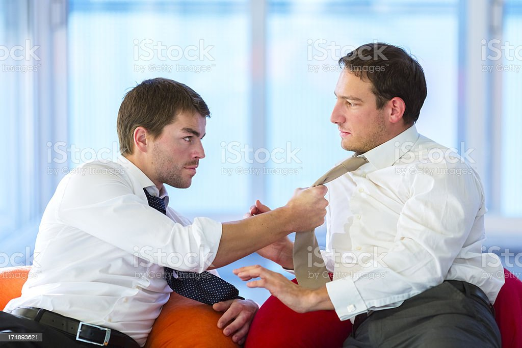 Businessman threatening co-worker in the office royalty-free stock photo