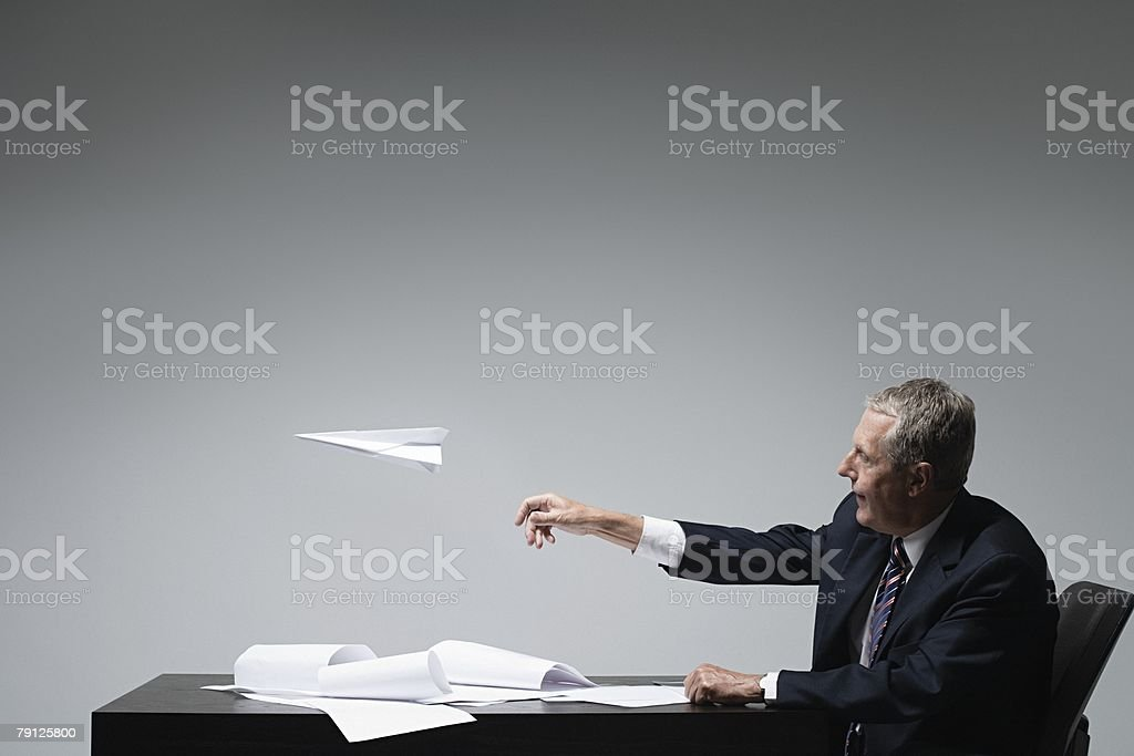 A businessman throwing a paper aeroplane royalty-free stock photo