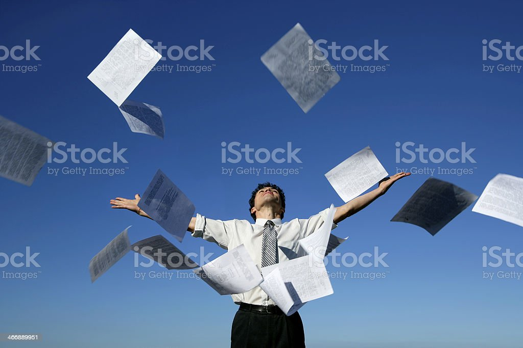 Businessman throwing papers into the air stock photo