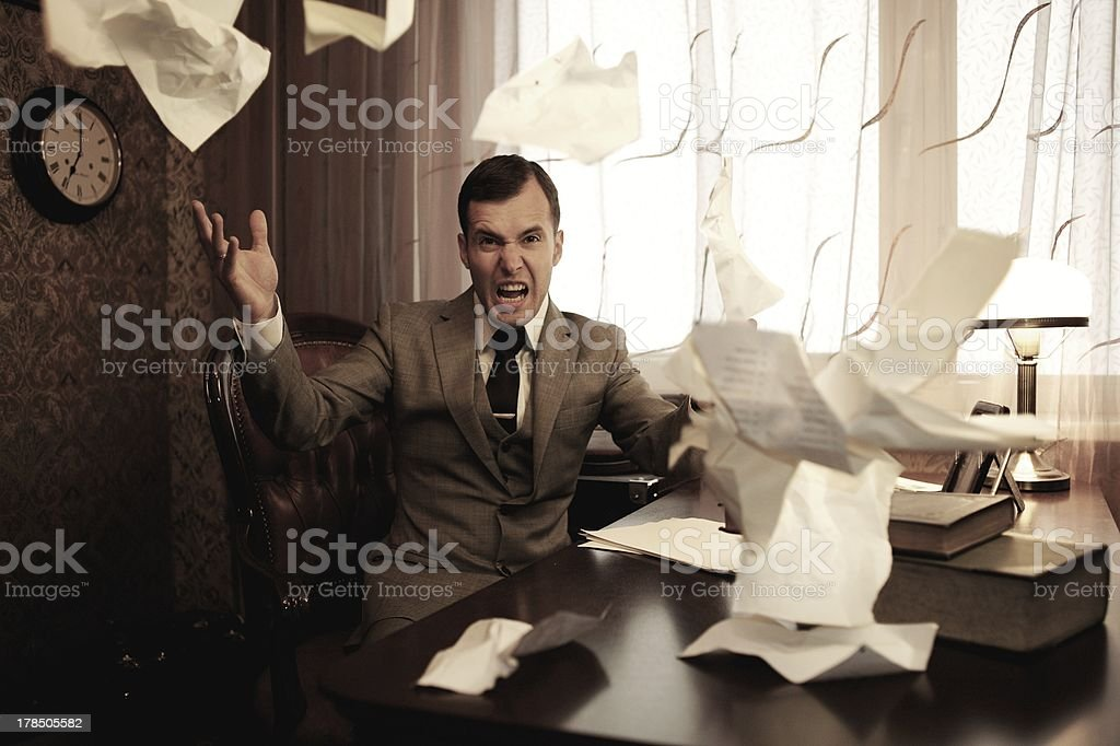 Businessman throwing papers into the air with an angry look  stock photo