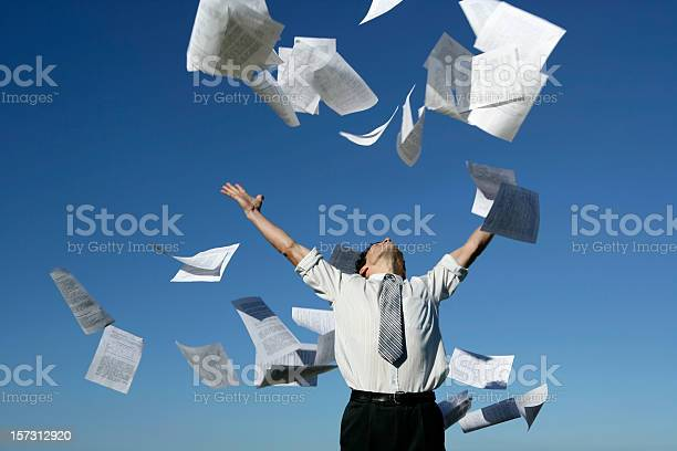 A young businessman throwing away his papers on a blue sky background.