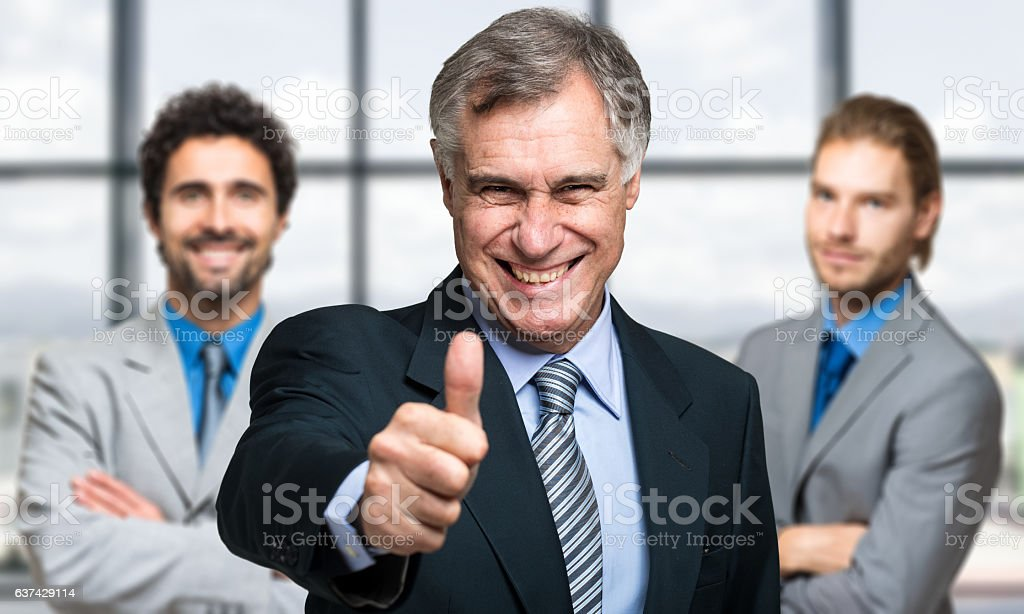Businessman thumbs up with his colleagues in the background stock photo