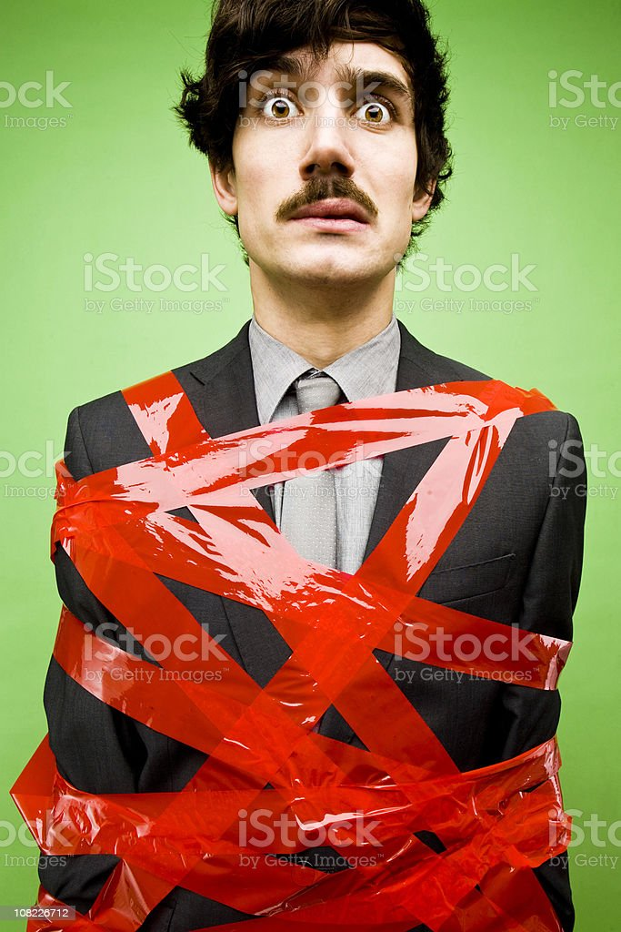 Businessman Tied Up in Red Tape stock photo