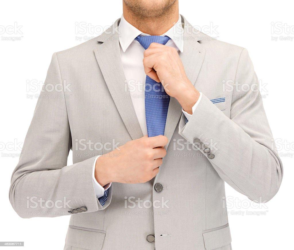 Businessman tightening blue tie stock photo