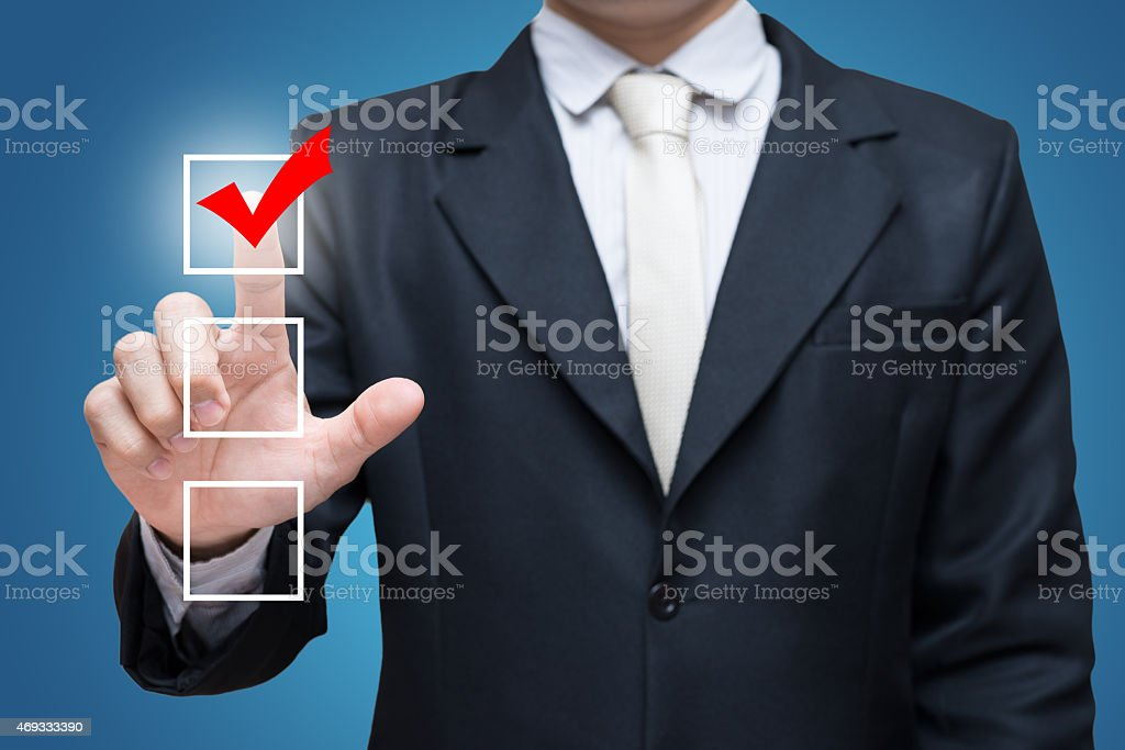 Businessman touch checking mark checklist marker Isolated on blue background stock photo