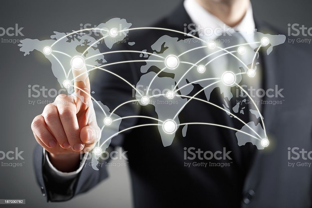 Businessman touches screen of connected continents stock photo