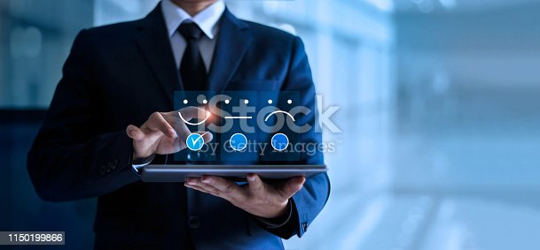 istock Businessman touching and drawing face emoticon smile on the tablet, service mind. blue background. Customer service concept. 1150199866