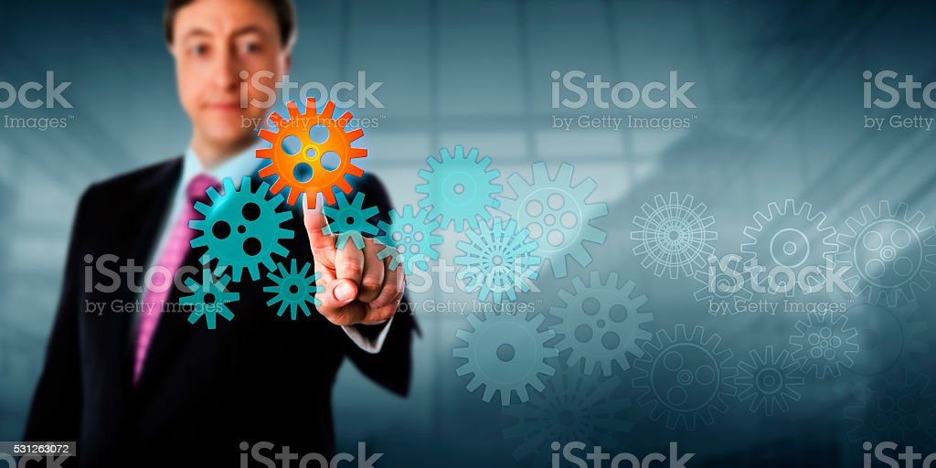 Businessman Touching Cog In A Virtual Gear Train stock photo