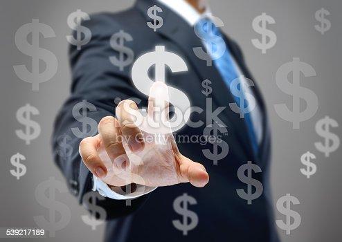 Businessman touching dollar signs on virtual screen.