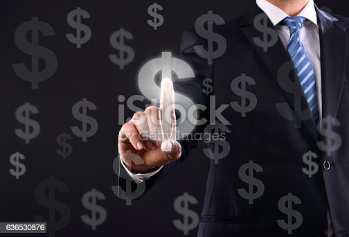 Businessman touching dollar signs on virtual screen on black background.