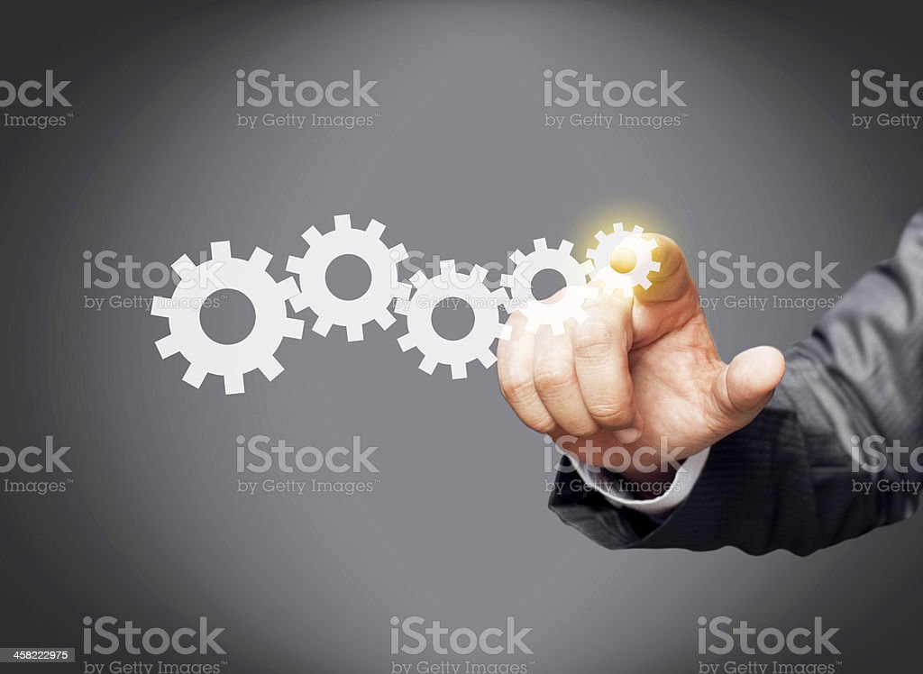 Businessman touching gear on screen stock photo