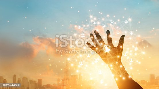 istock Businessman touching icon customer in hand with global network connection and data exchanges worldwide on city sunset background. Networking and technology concept 1025744866