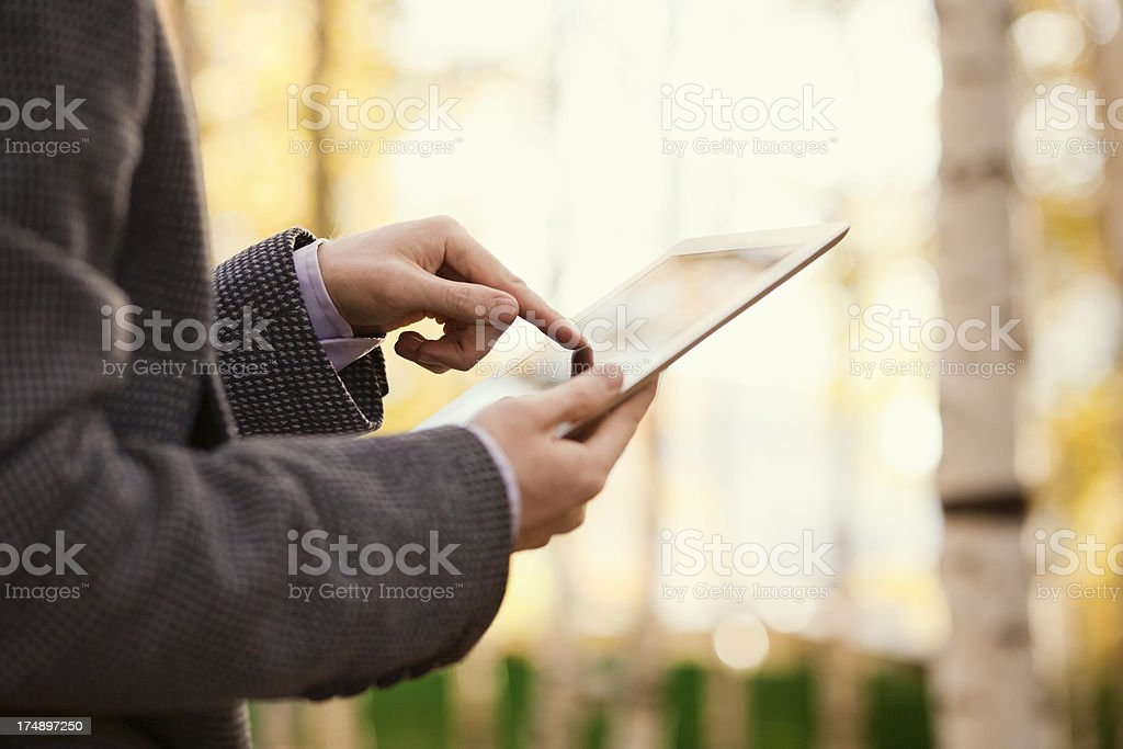 Businessman touching screen tablet PC Businessman touching screen tablet PC in park Adult Stock Photo