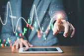 Businessman touching stock market technical chart on virtual screen of tablet for analysis financial information data , Value investor concept.
