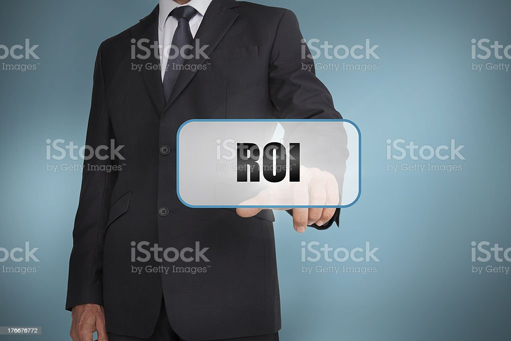 Businessman touching tag with roi written on it royalty-free stock photo