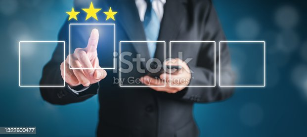 Businessman touching virtual screen with finger to select starred icons with ideas, strategies and technologies for future human business.