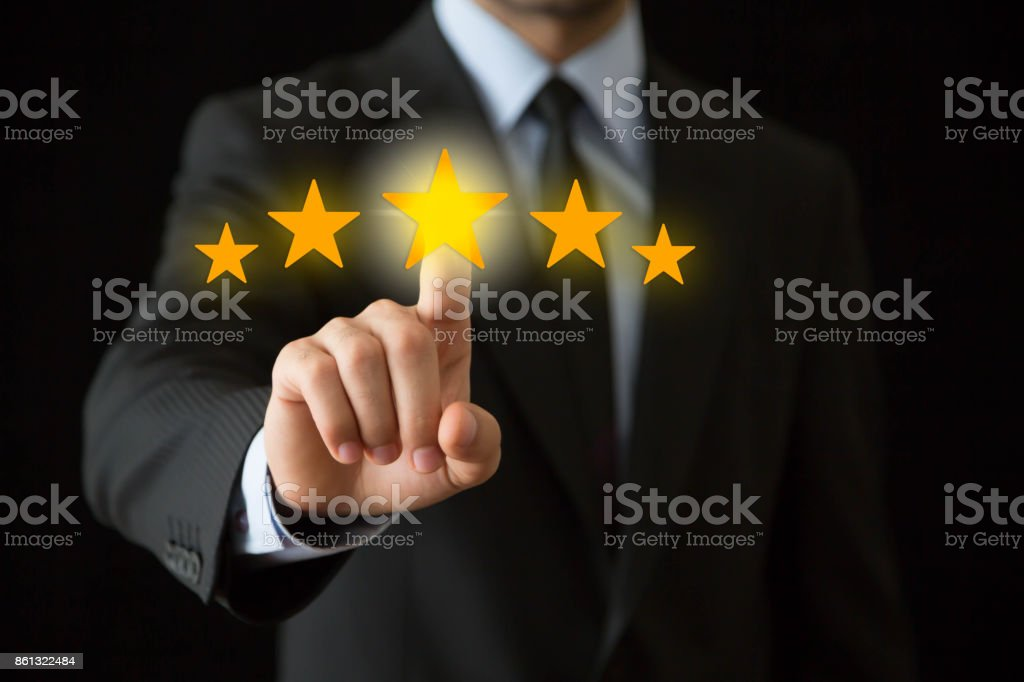 Businessman touchscreen gold stars stock photo