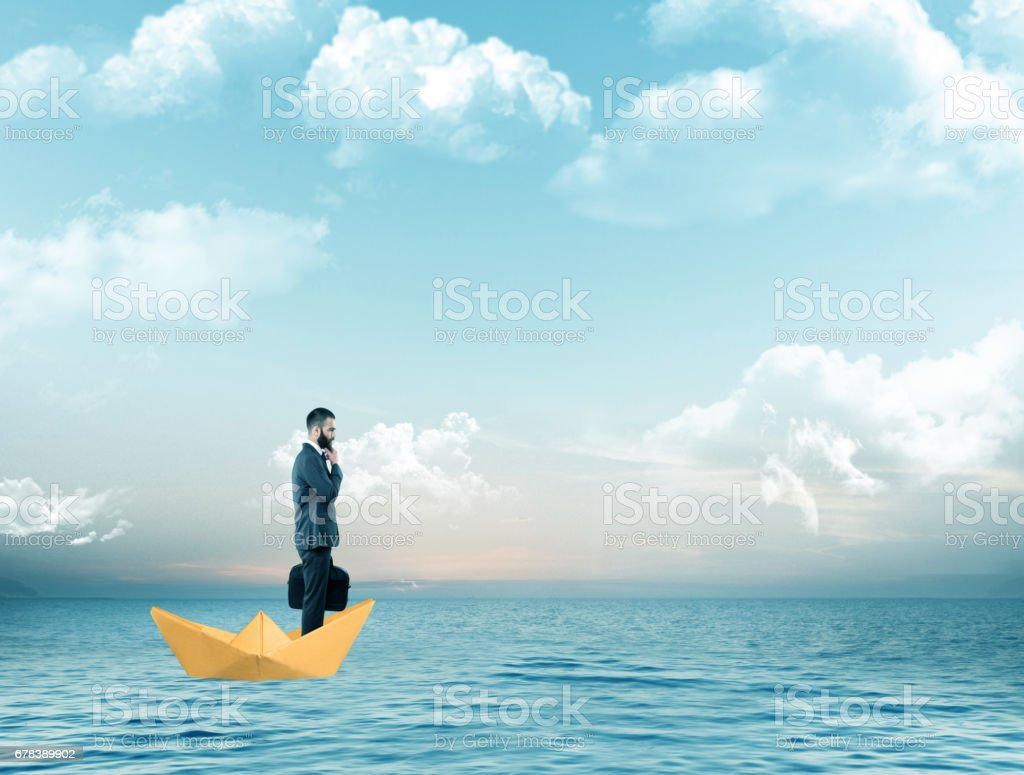 Businessman traveling on paper boat over sea