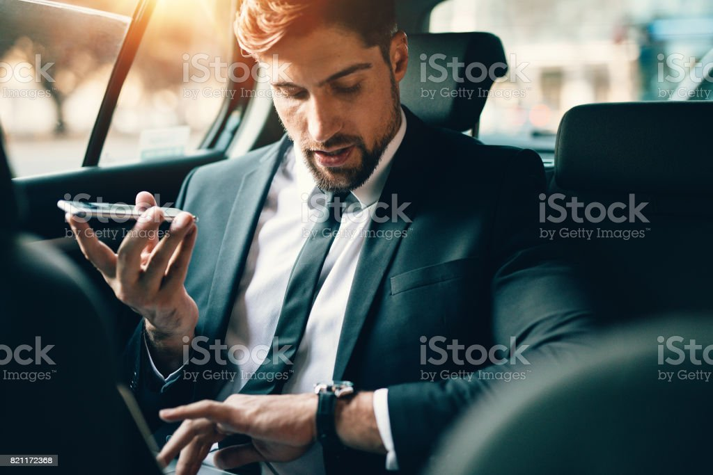 Businessman travelling by car using smart phone and checking time stock photo