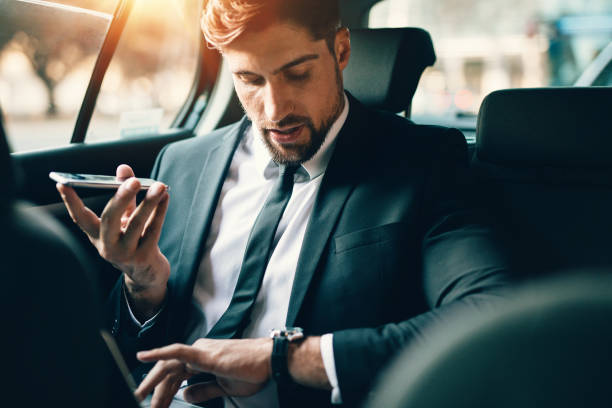 businessman travelling by car using smart phone and checking time - watch timepiece stock photos and pictures