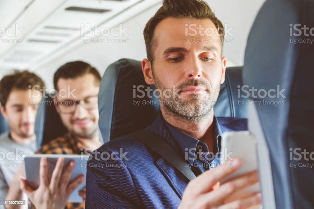 Businessman travelling by flight using smart phone stock photo