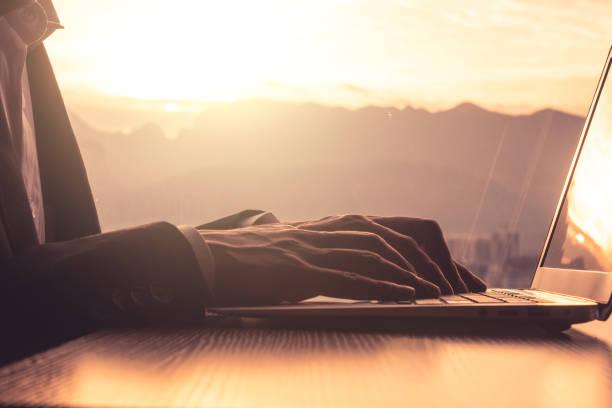 Geschäftsmann tippt bei Sonnenuntergang auf einem Laptop – Foto