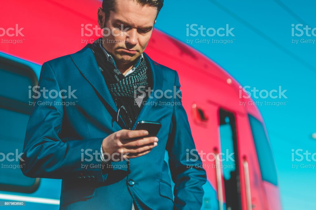 Serious businessman using cell phone and reading message while...