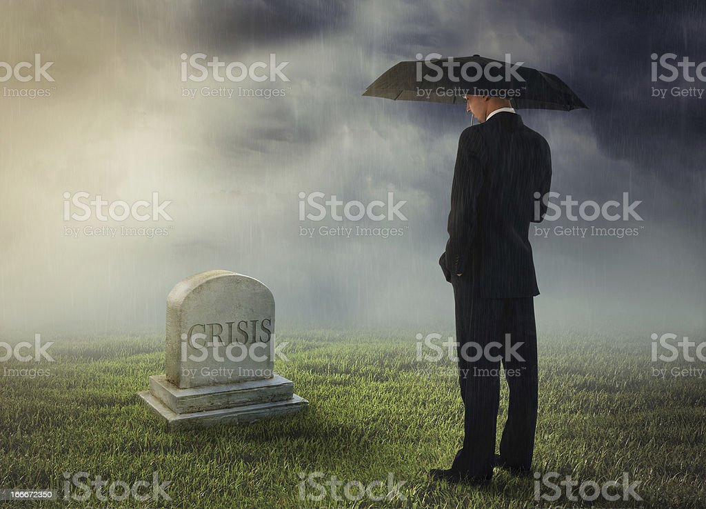 Businessman under umbrella at a tomb with 'CRISIS' engraved royalty-free stock photo