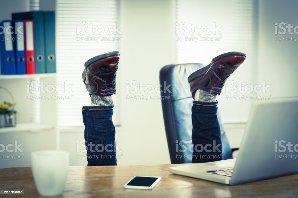 Businessman upside down at his desk stock photo