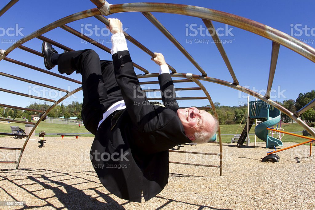 Businessman Upside Down in Playground stock photo
