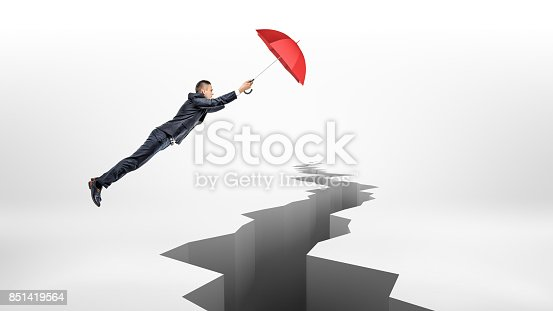 istock A businessman uses a large red umbrella to fly over a long earthquake crack on white background 851419564