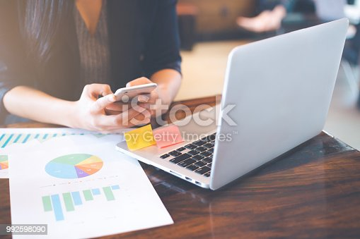 996183898 istock photo Businessman uses a phone to work on charts and graphs that show results. 992598090