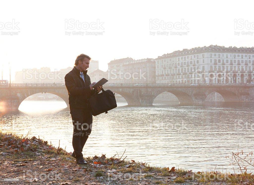 Businessman uses digital tablet beside river, sunrise - foto stock
