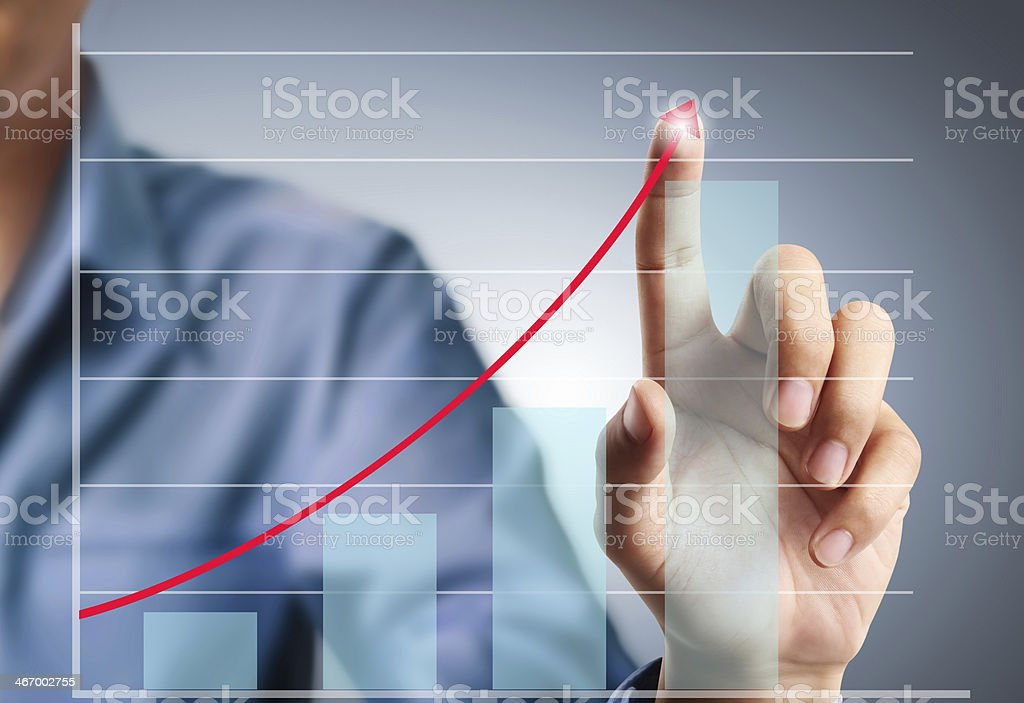Businessman uses finger to push graph upward stock photo