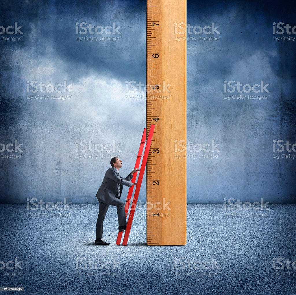 Businessman Uses Ladder To Climb Wooden Ruler stock photo